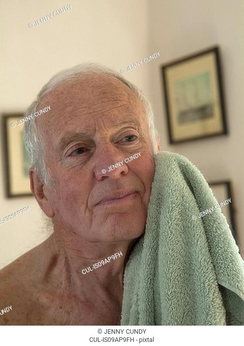 Senior man drying face with towel