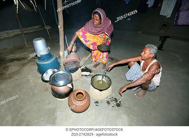 Woman cooking sea shells, KHARIA TRIBE, Khadiyapara village, Chattisgarh, India