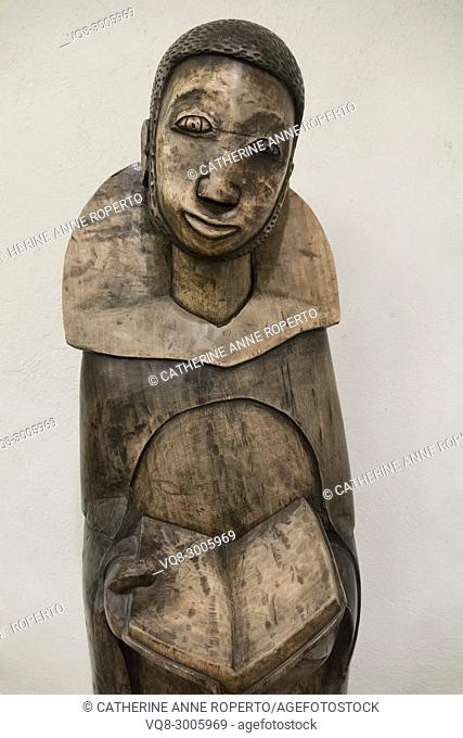 Polished wooden carving of African saint holding an open Bible in the crypt chapel of St Martin-in-the-Fields, Trafalgar Square, London, England