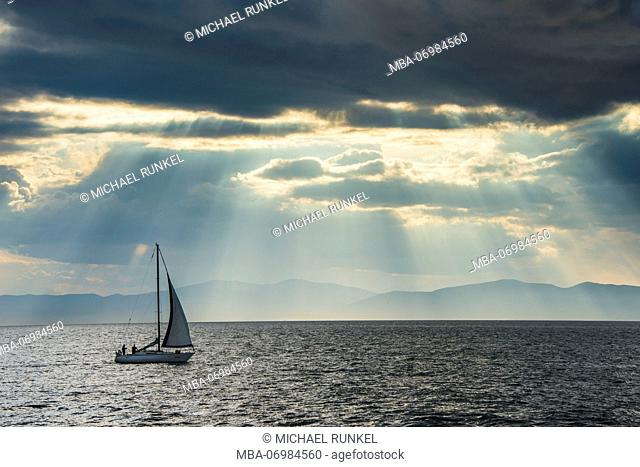 Sailing boat before the sun breaking through the clouds above the Amur in Vladivostok, Russia