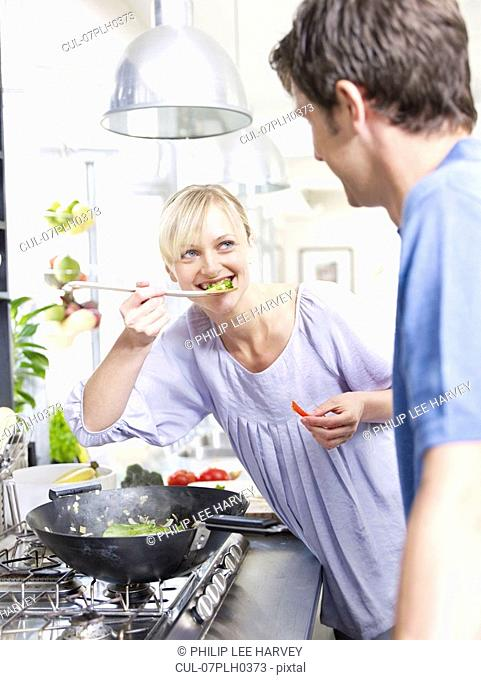 Man and woman in kitchen cooking food