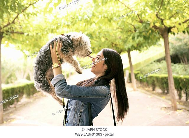 Happy young woman with her dog in a park