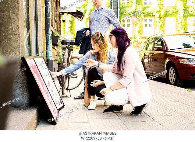 Women looking at signboard