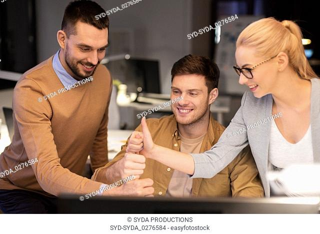 business team making thumbs up gesture at office