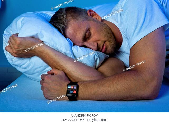 Man Sleeping With Smart Watch In His Hand Showing Heartbeat Rate