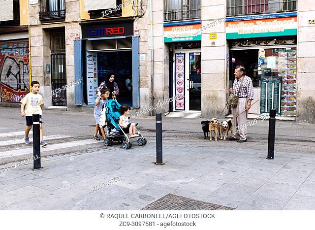 Muslim family walking down a street while local senior man with his dogs are standing in front of indian restaurant, in El Raval neighborhood, Barcelona