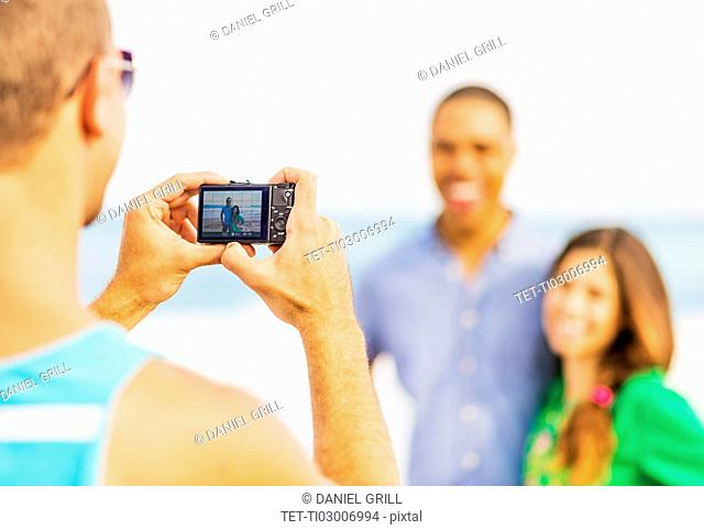 Young man taking photo of couple on beach
