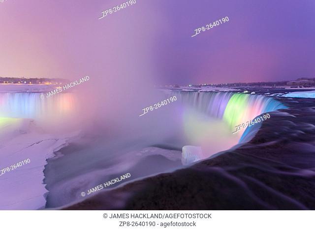 Horseshoe Falls illuminated at dusk with a frozen Niagara River. Niagara Falls, District Municipality of Niagara, Ontario, Canada