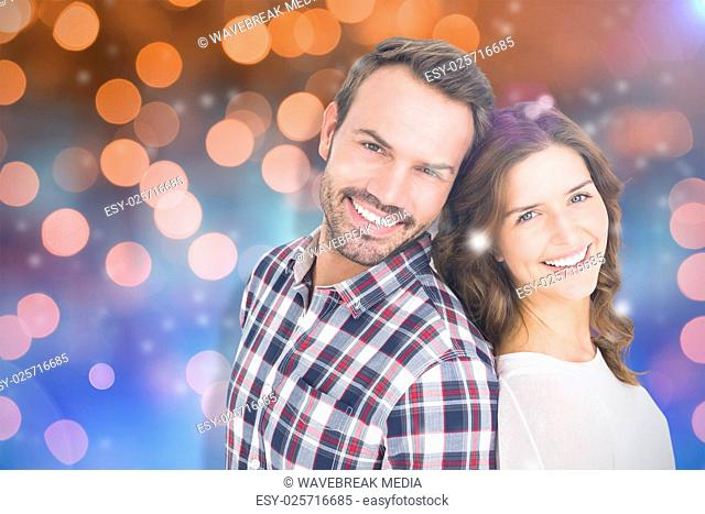 Composite image of close up of happy young couple standing back to back