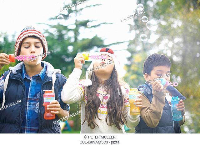 Siblings blowing bubbles in garden
