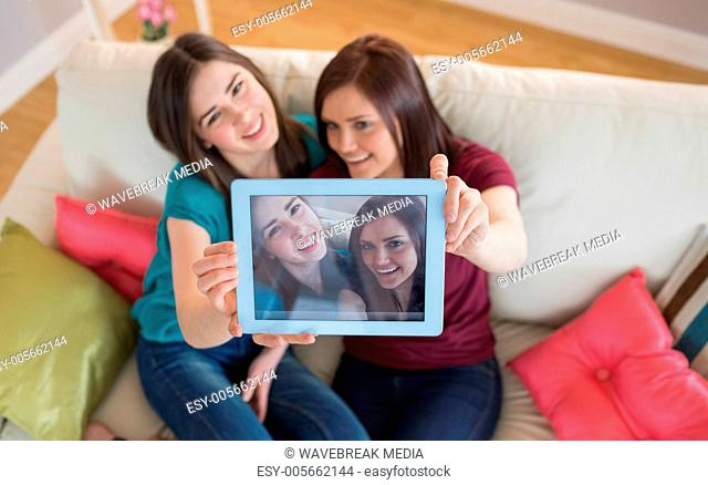 Two smiling friends on the couch taking a selfie with tablet pc