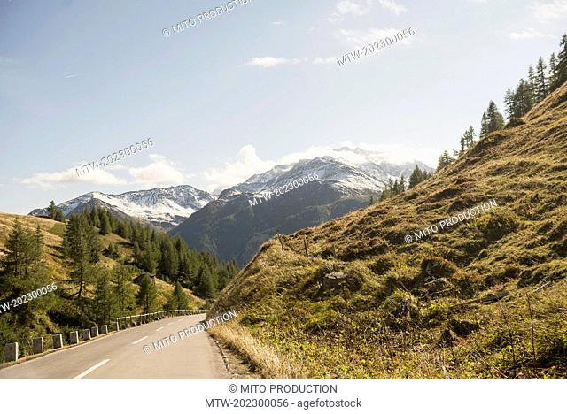 Road passing through mountains against cloudy sky, Grossglockner, Austrian Alps, Carinthia, Austria