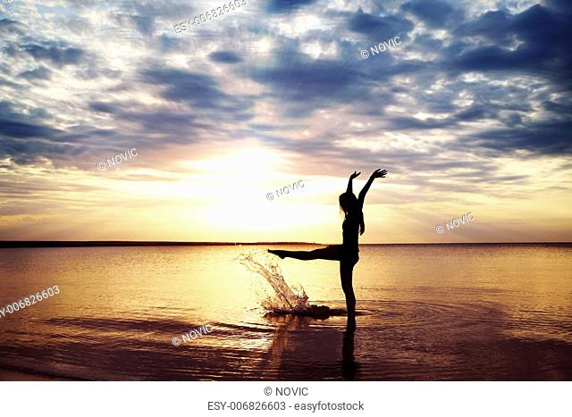 Sunset and elegant girl playing with water