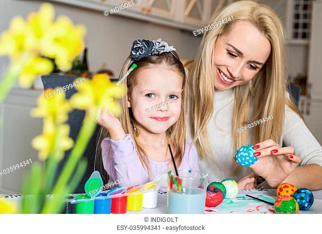 Young mother and her beautiful daughter painting Easter eggs. Easter, family, holiday and child concept