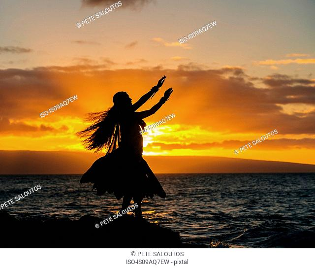 Silhouetted young woman in traditional costume, hula dancing on coastal rock at sunset, Maui, Hawaii, USA