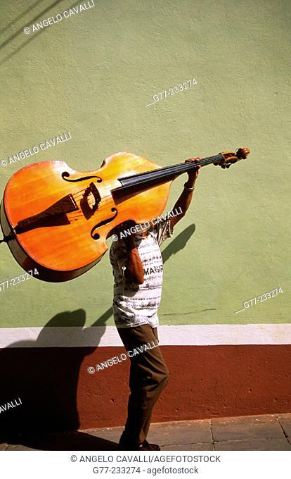 A bass player carrying his double bass. Trinidad de Cuba. Cuba