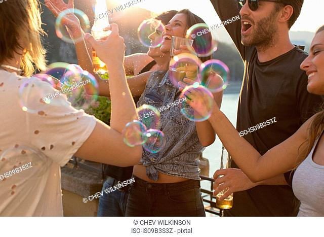 Adult friends playing with floating bubbles at roof terrace party