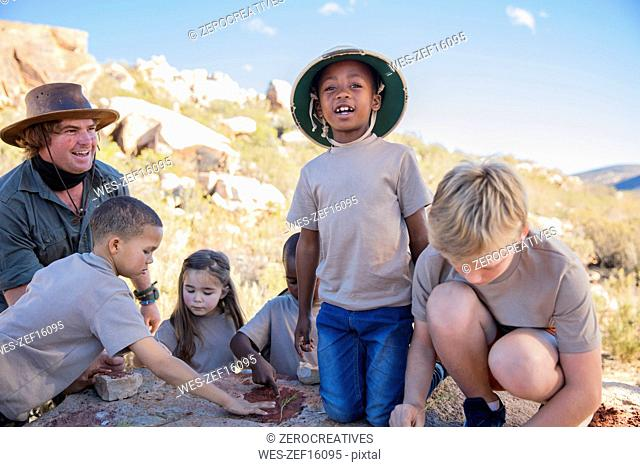 Children at a camp learning from guide