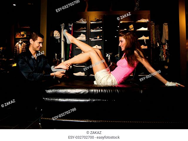 Young man dressing on new shoes to his girl friend. Both of them are smiling. Reflection of the woman in the mirror doesn't have smile because she is not so...