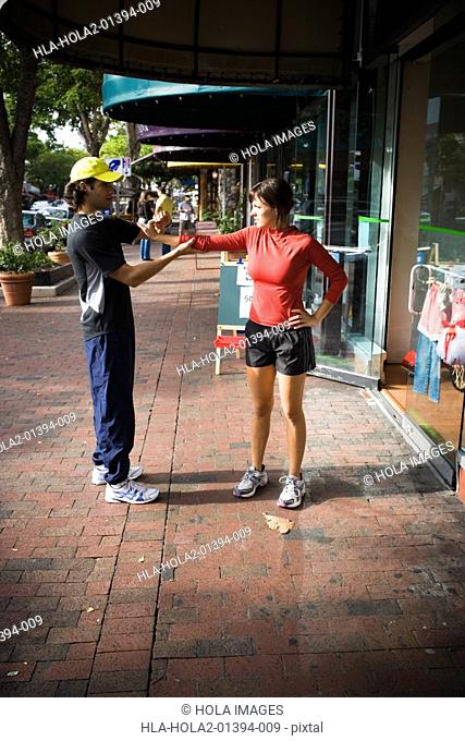 Young woman exercising with physical trainer