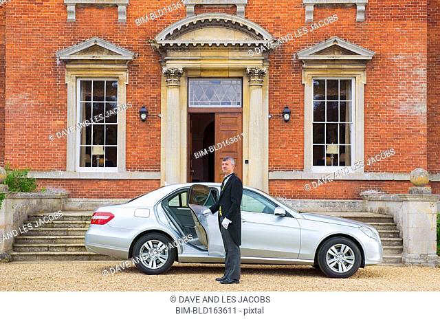 Caucasian butler opening car door outside mansion
