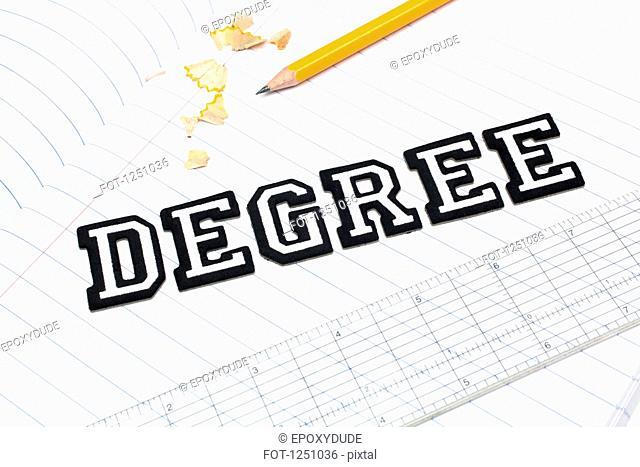 Varsity font stickers spelling out Degree atop a lined paper notebook with ruler and pencil