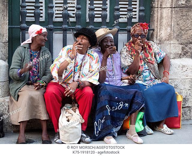 Four female friends sitting around smoking cigars