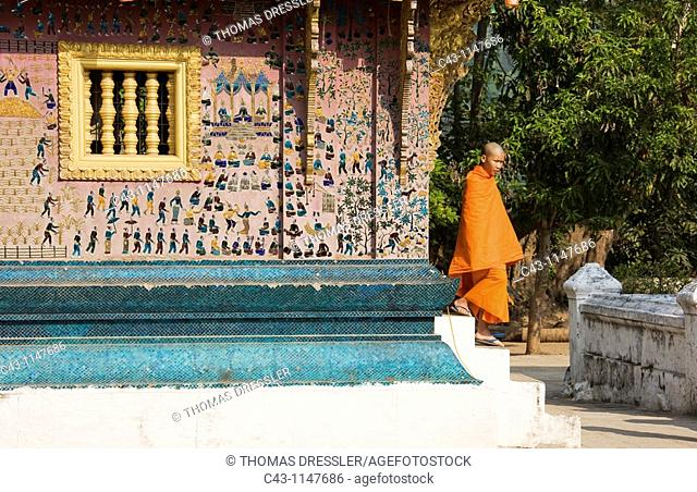 Laos - A Buddhist novice next to a wall decorated with glass mosaics in the Buddhist monastery of Vat Xieng Thong, Luang Prabangs oldest and most splendid...