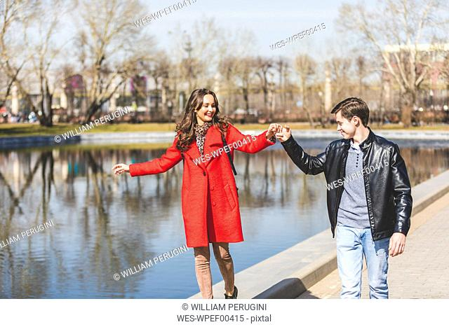Russia, Moscow, couple dating and having fun at park, young man holding woman's hand