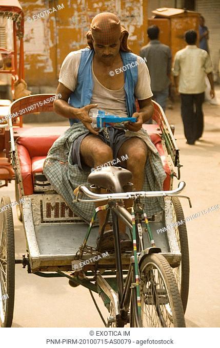 Rickshaw puller sitting on rickshaw, Chandni Chowk, Delhi, India