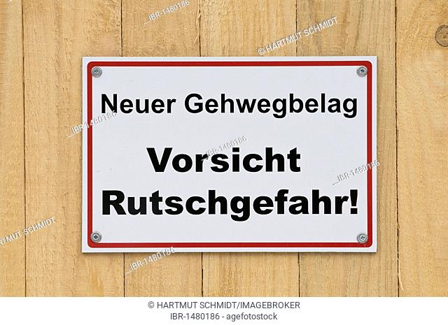 Sign on wooden board fence, Neuer Gehwegbelag Vorsicht Rutschgefahr, new walkway surface, caution slip hazard!