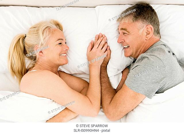 Mature couple holding hands in bed