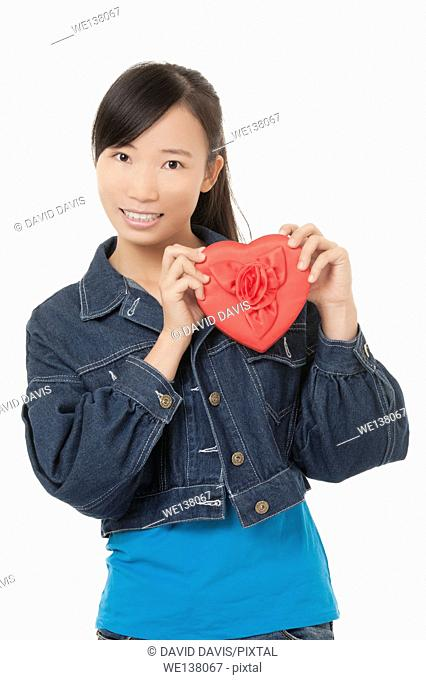 Beautiful Chinese woman holding a red heart and flirting with someone isolated on a white background
