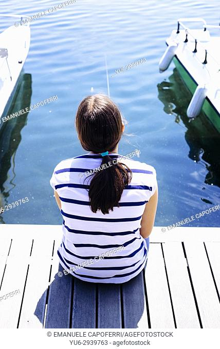 girl fishing in the lake of Monate., Italy