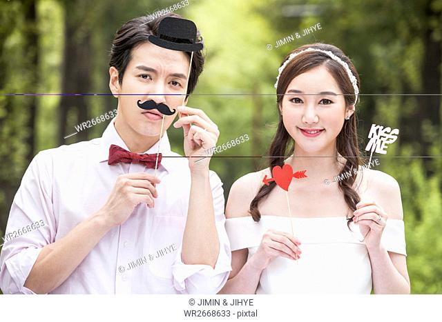 Portrait of young smiling wedding couple posing outdoors