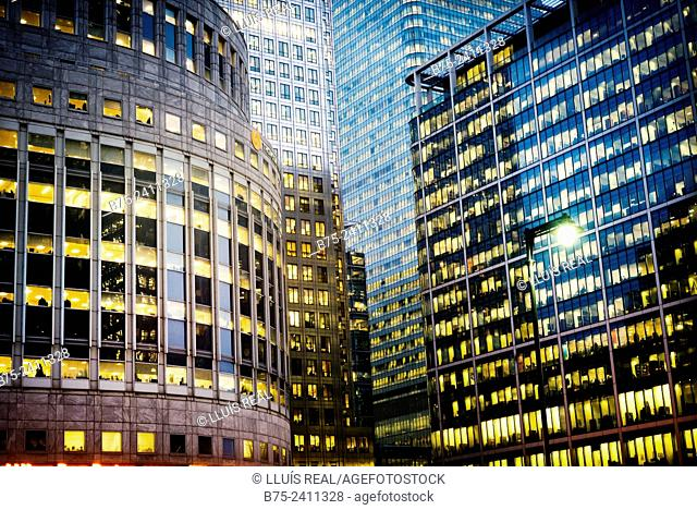 Closeup of several office buildings with lots of windows with lights on in the evening in Canary Wharf, London, England, UK, Europe