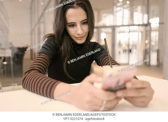 portrait of positive minded woman using phone while taking a break at table in café, in Munich, Germany