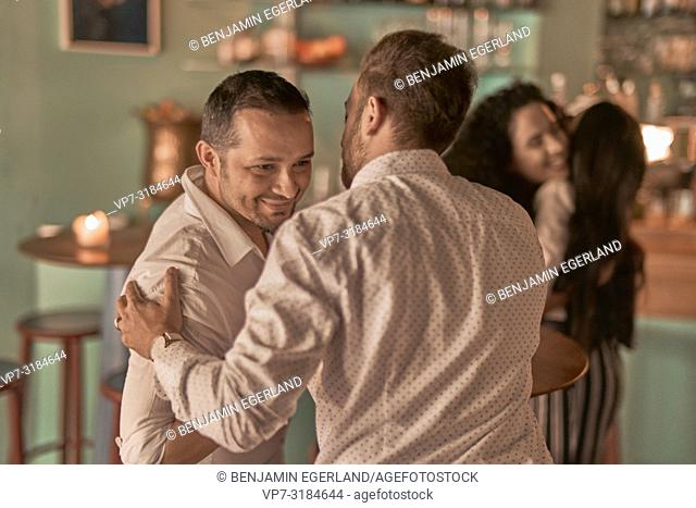 two men, friends greeting at bar, in Kismet, Munich, Germany