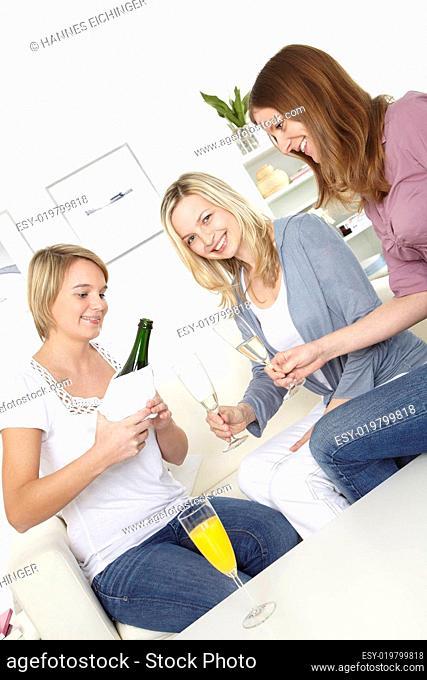 drei freundinnen trinken sekt und orangensaft