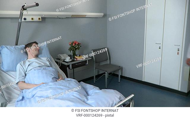 Medium lockdown shot of a patient lying in bed when a doctor and nurse walk in consult his chart