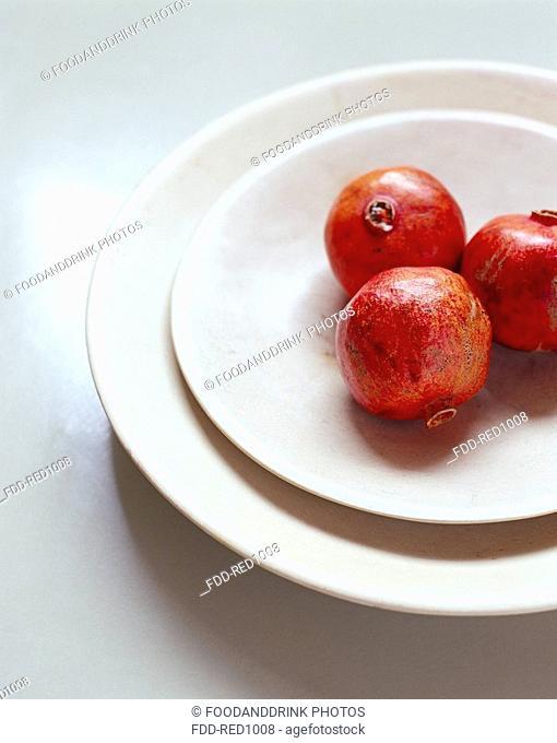 Three pomegranates on white china plates