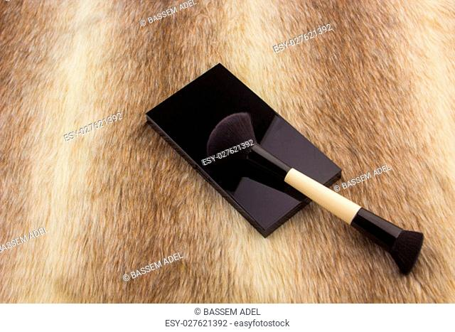Makeup tools on Fur background / featuring eyeshadow palette, lipstick, makeup brushes on a fury background