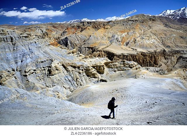 Trekker and mineral landscape between Lo Manthang and the village of Dhie Gaon. Nepal, Gandaki, Upper Mustang (near the border with Tibet)