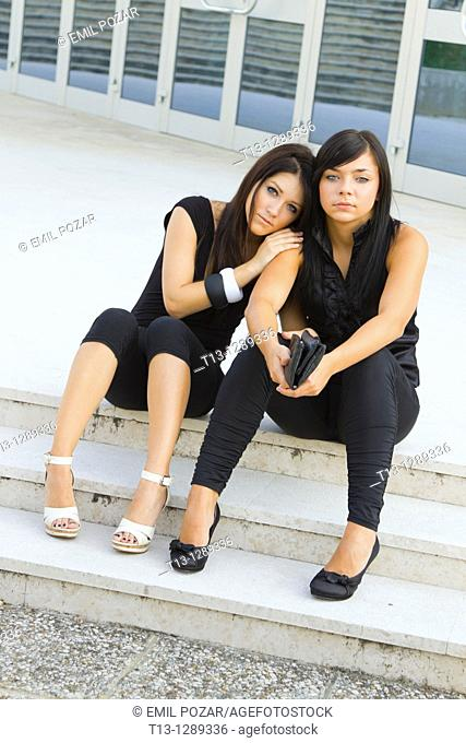 Two young women are sitting on the street