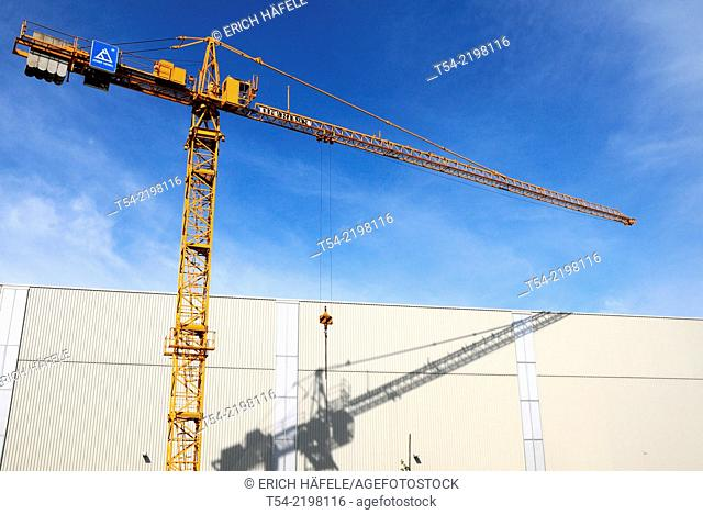 Yellow construction crane company Liebherr soars in the blue sky