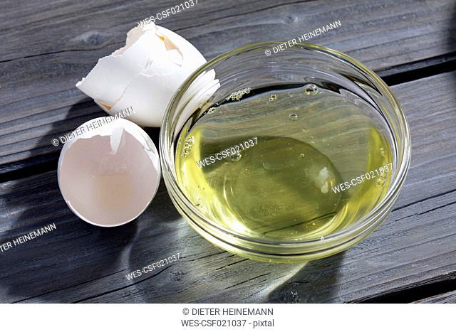 Bowl of egg white and eggshells on grey wood