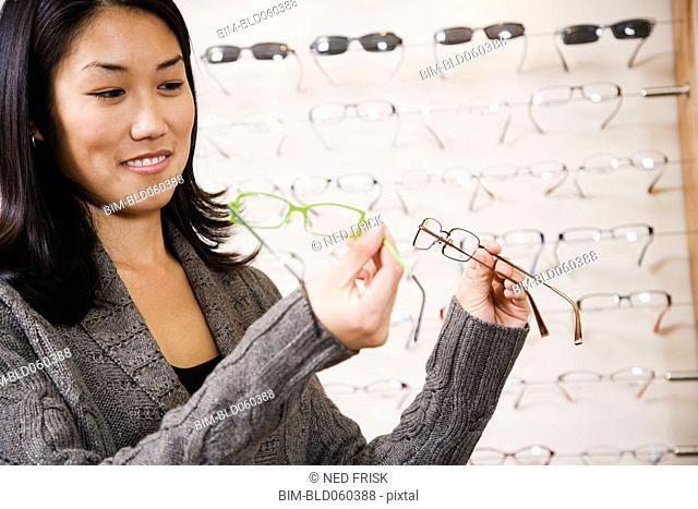 Asian woman comparing eyeglasses