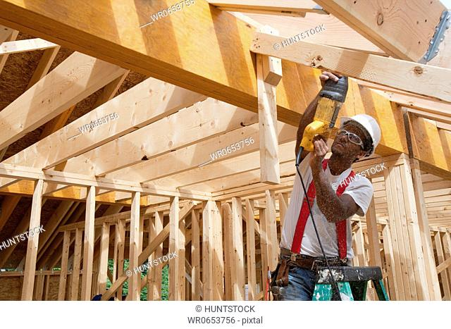 Hispanic carpenters using reciprocating saw on a roof rafter at a house under construction