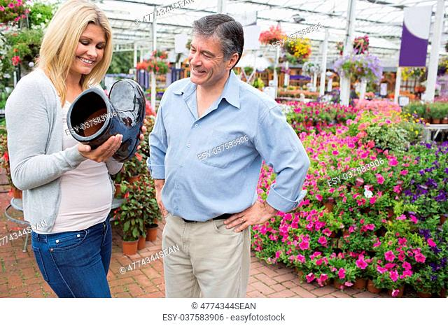 Couple smiling and looking at boot shaped flower pot in garden center