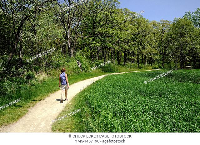 Woman walking hiking trail around a glacial bog at Moraine Hills State Park in McHenry, Illinois, USA
